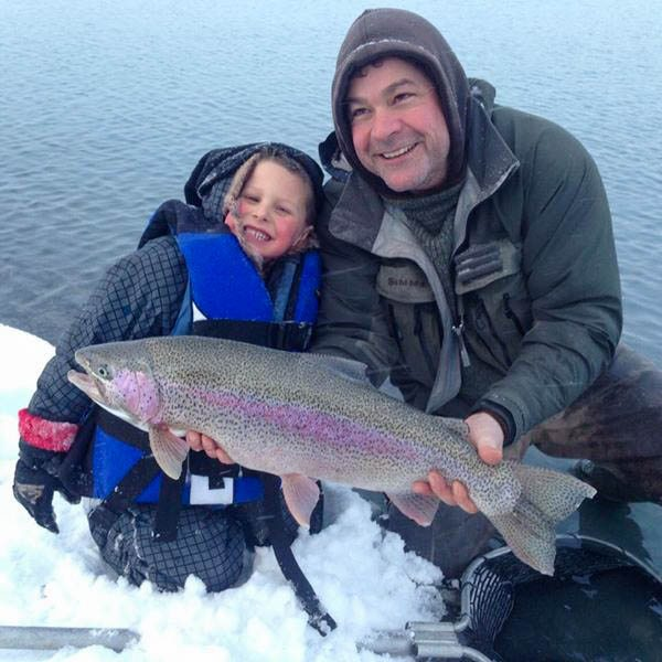 Captain Reubin Payne and son with a rainbow trout